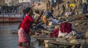 En ung man arbetar som en dhobi- eller tvätteriman på kanten av Gangeset River i Varanasi Arkivbilder