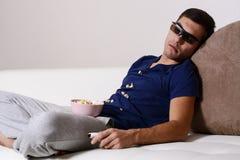 En ung man avverkar sovande, medan hålla ögonen på TV i exponeringsglas 3D med popcorn spritt på skjortan Arkivfoton