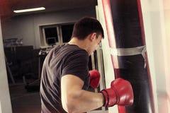 En ung man boxas en påse arkivfoto