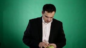 En ung man finner pengar i en bok Grön bakgrund arkivfilmer