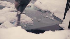 En ung man gör ren fönstret av bilen från snön arkivfilmer