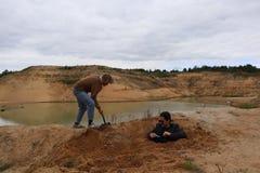 En ung man gräver ett hål med en skyffel royaltyfri fotografi