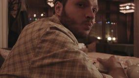 En ung man håller ögonen på i ett kafé lager videofilmer