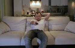 En ung man hemma som sitter på en soffa i aftonen med fjärrkontrollen i hans hand som ser direkt på kameran arkivbilder