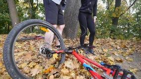 En ung man hjälper en kvinna som har stupat från en cykel arkivfilmer