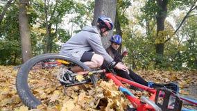 En ung man hjälper en kvinna som har stupat från en cykel lager videofilmer
