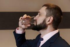 En ung man i en affärsdräkt är dricksvatten från ett exponeringsglas fotografering för bildbyråer