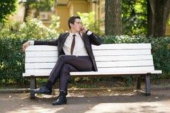 En ung man i en affärsdräkt lämnade kontoret och kom till parkera han sitter på en vit bänk bara och talar på telefonen royaltyfri bild