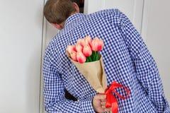 En ung man i en blå plädskjorta och jeans som rymmer en bukett av tulpan bak hans baksida och tittar i den öppna dörren arkivfoto