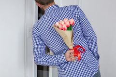 En ung man i en blå plädskjorta och jeans som rymmer en bukett av tulpan bak hans baksida och tittar i den öppna dörren royaltyfri fotografi