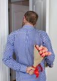 En ung man i en blå plädskjorta och jeans som rymmer en bukett av tulpan bak hans baksida och tittar i den öppna dörren royaltyfri foto