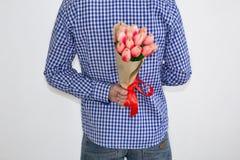 En ung man i en blå plädskjorta och jeans som rymmer en bukett av tulpan, i hans hand bak hans baksida, på en vit bakgrund royaltyfri fotografi