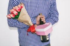 En ung man i en blå plädskjorta som rymmer en bukett av tulpan, en gåva och en flaska av vin, i hans hand bak hans baksida royaltyfria bilder
