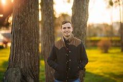 En ung man i en parkera i ett mörker - blå skjorta Vår Royaltyfri Fotografi