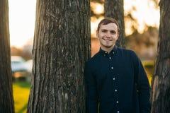 En ung man i en parkera i ett mörker - blå skjorta Vår Royaltyfri Foto