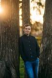 En ung man i en parkera i ett mörker - blå skjorta Vår Fotografering för Bildbyråer