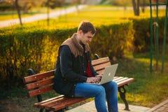 En ung man i en parkera i ett mörker - blå skjorta Vår Arkivbild