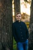 En ung man i en parkera i ett mörker - blå skjorta Vår Royaltyfri Bild
