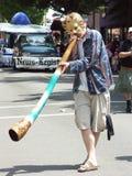 En ung man i en ståta som blåser ett australiskt horn Arkivfoton