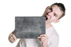 En ung man i en T-tröja med ett baner för din text eller någonting annat, försöker att bita ett baner Horisontal inrama Fotografering för Bildbyråer
