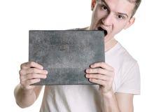 En ung man i en T-tröja med ett baner för din text eller någonting annat, försöker att bita ett baner Horisontal inrama Arkivfoto