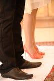 En ung man i enorma skor och en flicka i röda skor kom till den ortodoxa kyrkan Royaltyfria Foton