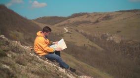En ung man i ett gult omslag, jeans och exponeringsglas sitter i bergen och ser översikten för handelsresande s stock video
