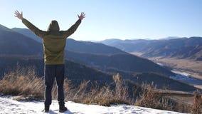 En ung man i ett omslag som överst står av ett berg, ser ut in i avståndet och känner frihet och glädje från a arkivfilmer
