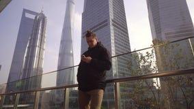 En ung man i ett svart omslag använder en telefon på bakgrunden av skyskrapor i Shanghai, Kina stock video