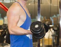 En ung man i idrottshallen som pumpar muskler royaltyfri bild