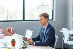 En ung man i kontoret mottar en gåva Fotografering för Bildbyråer