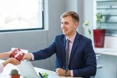 En ung man i kontoret mottar en gåva Arkivbilder