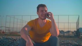 En ung man i en orange T-tr?ja och jeans vid havet p? v?ren Grabben talar p? telefonen arkivfilmer