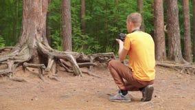 En ung man i skogen tar bilder av rotar av ett träd lager videofilmer
