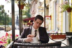 En ung man i en svart affärsdräkt, en vit skjorta och ett band sitter i ett stadsgatakafé på en tabell och tycker om en kopp kaff arkivbilder