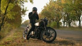 En ung man i svart läderomslag kommer upp till hans motorcykel, sitter där och sätter en svart hjälm och solglasögon för arkivfilmer