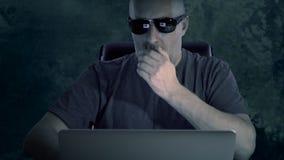 En ung man i en T-tröja och exponeringsglas sitter på datoren En man arbetar på en dator sent i mörkret på natten och lager videofilmer