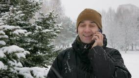 En ung man i vinterskog som talar på telefonen Stora snowfall Han beundrar sidorna av snö och träd En man i ett mörker stock video
