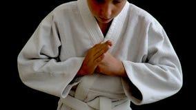 En ung man i en vit kimono står på en mörk bakgrund, är hans framsida och ben inte synliga, och hans händer fälls ned arkivfilmer