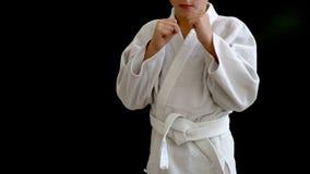 En ung man i en vit kimono står på en mörk bakgrund, faller är hans händer nedanför hans bröstkorg och i rörelse Barnet arkivfilmer