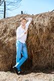 En ung man i en vit skjorta och blåttflåsanden lutade mot en höstack arkivfoto