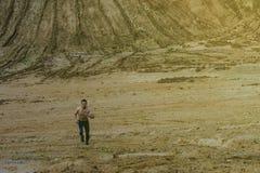 En ung man kör i en sandig kanjon i grå strumpbyxor Begreppet av en sund livsstil Royaltyfri Fotografi