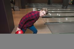 En ung man kastar en bowlingklot Student som spelar bowling Fotografering för Bildbyråer