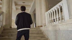 En ung man klättrar trappan och tar foto av en övergiven herrgård arkivfilmer