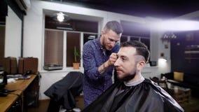 En ung man kom till frisersalongen för att få en stilfull frisyr och innegrej som utformar från en yrkesmässig frisör arkivfilmer