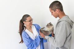 En ung man kommer med en katt till en veterinär Royaltyfria Bilder