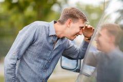 En ung man kontrollerar en använd bil Tema för använd bil Royaltyfri Foto