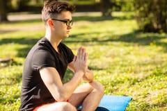 En ung man kopplar av, och g?ra yoga i det gr?nt parkera begrepp av en sund livsstil royaltyfri bild