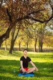 En ung man kopplar av, och g?ra yoga i det gr?nt parkera begrepp av en sund livsstil arkivbilder