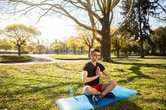 En ung man kopplar av, och g?ra yoga i det gr?nt parkera begrepp av en sund livsstil royaltyfria bilder